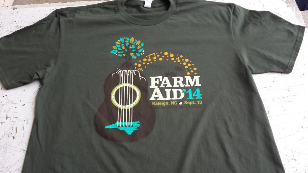 The shirt of the 2014 Farm Aid Logo Shirt uses the same elements as the poster but it specifically for the shirt design.