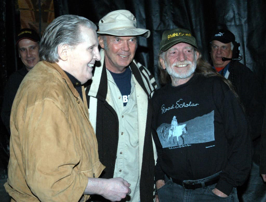 "Willie Nelson standing with Neil Young. Willie is wearing the Minimum Wage Art shirt ""Road Scholar"" that we printed."